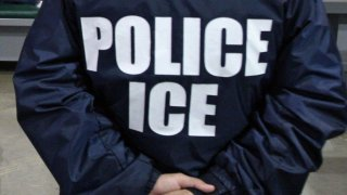 An Immigration and Customs Enforcement officer guards immigrants