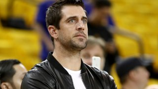 In this June 17, 2017, file photo, quarterback Aaron Rodgers of the Green Bay Packers watches warm-ups before the Golden State Warriors take on the Cleveland Cavaliers in Game 5 of the 2017 NBA Finals at ORACLE Arena in Oakland, California.