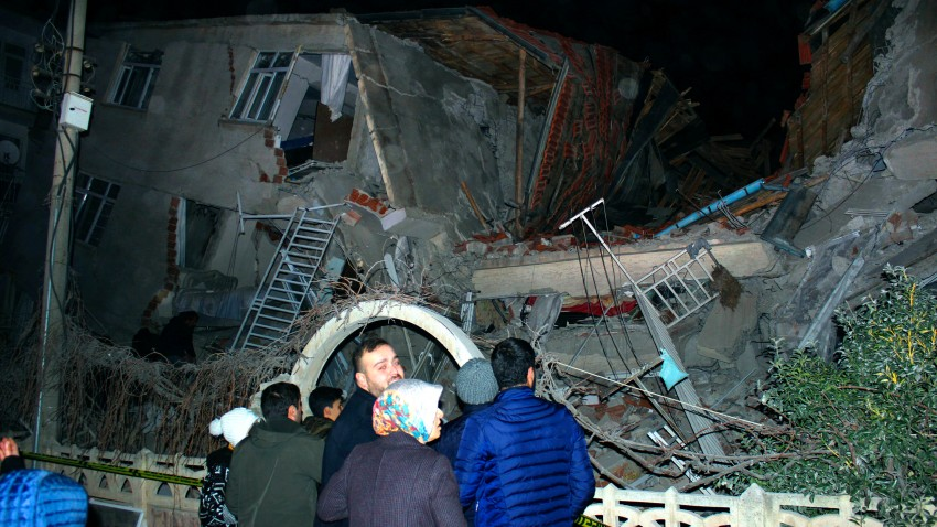 People look at a collapsed building after a 6.8 earthquake struck Elazig city center in eastern Turkey, Friday, Jan. 24, 2020.