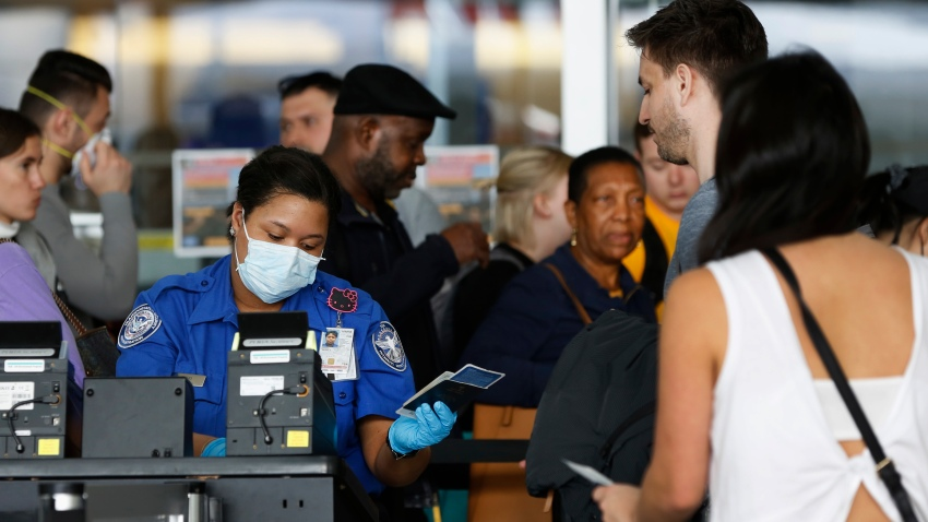In this Saturday, March 14, 2020 file photo, a Transportation Security Administration agent hands a passport back to a traveler as she screens travelers, at a checkpoint inside an airline terminal at John F. Kennedy Airport in New York.