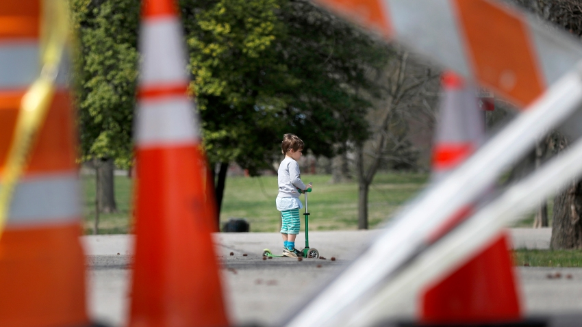 a child rides a scooter past barricades at an entrance to Tower Grove Park in St. Louis.