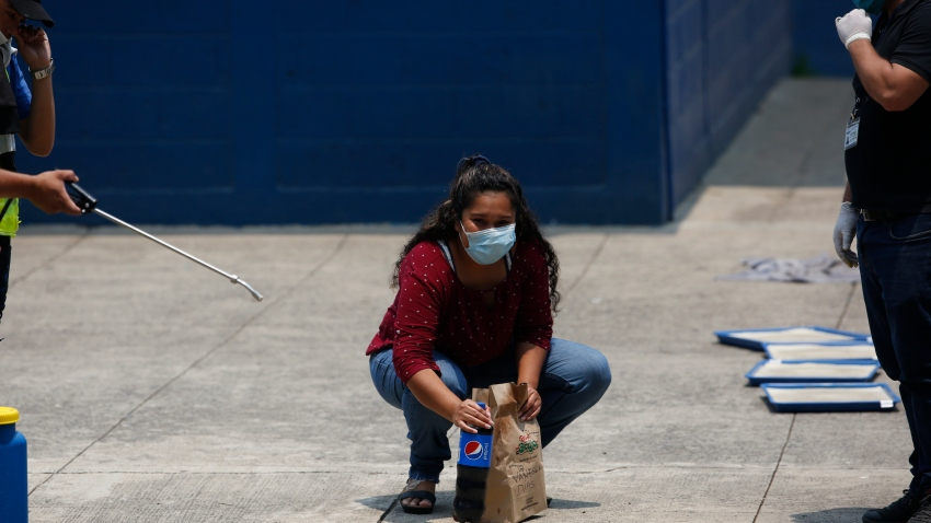 A deported woman looks at her family as she picks up the food they brought her, at the site where Guatemalans returned from the U.S. are being held in Guatemala City, Friday, April 17, 2020.