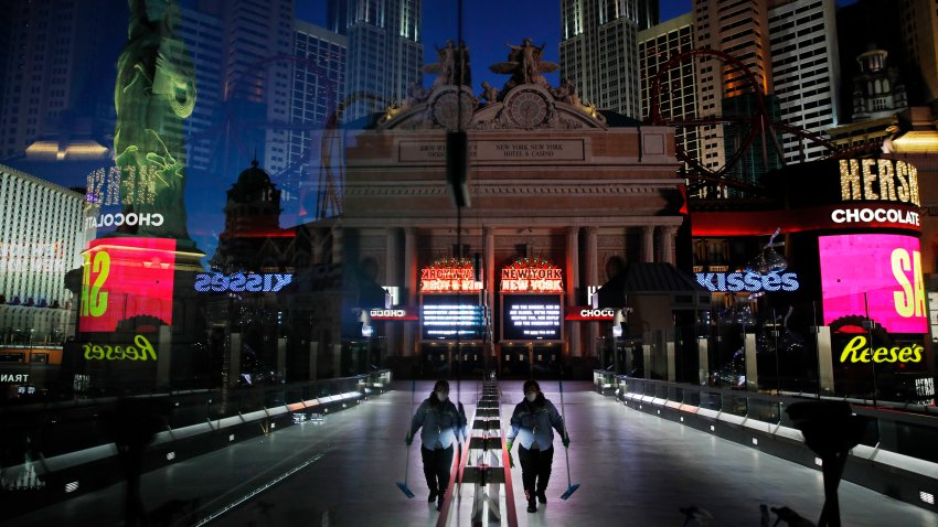 A lone worker wearing a mask cleans a pedestrian walkway devoid of the usual crowds as casinos and other business are shuttered due to the coronavirus outbreak in Las Vegas.