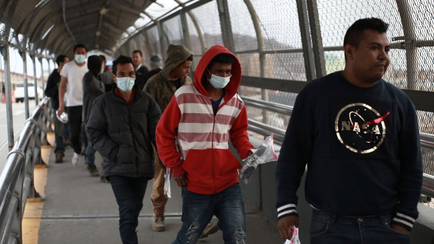 In this Saturday, March 21, 2020 file photo, Central American migrants seeking asylum, some wearing protective face masks, return to Mexico via the international bridge at the U.S-Mexico border that joins Ciudad Juarez and El Paso