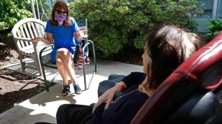 Marcie Abramson, left, gestures as she speaks to her mother, Cynthia, outdoors at the Hebrew Rehabilitation Center, Wednesday June 10, 2020, in Boston, under the state's new nursing home visitation guidelines which requires social distancing. The two haven't been able to visit in person since March.