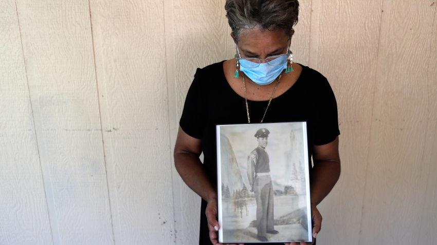 In this May 18, 2020, file photo, Belvin Jefferson White poses with a portrait of her father Saymon Jefferson at Saymon's home in Baton Rouge, La. Belvin recently lost both her father and her uncle, Willie Lee Jefferson, to COVID-19. African Americans are disproportionately likely to say a family member or close friend has died of COVID-19 or respiratory illness since March, according to a series of surveys conducted since April that lays bare how black Americans have borne the brunt of the pandemic.