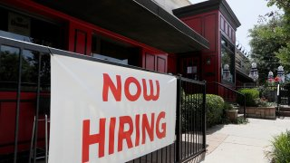 """In this June 26, 2020, file photo, Sherlock's, a pub in Addison, Texas, has a sign out front that reads, """"Now Hiring."""""""