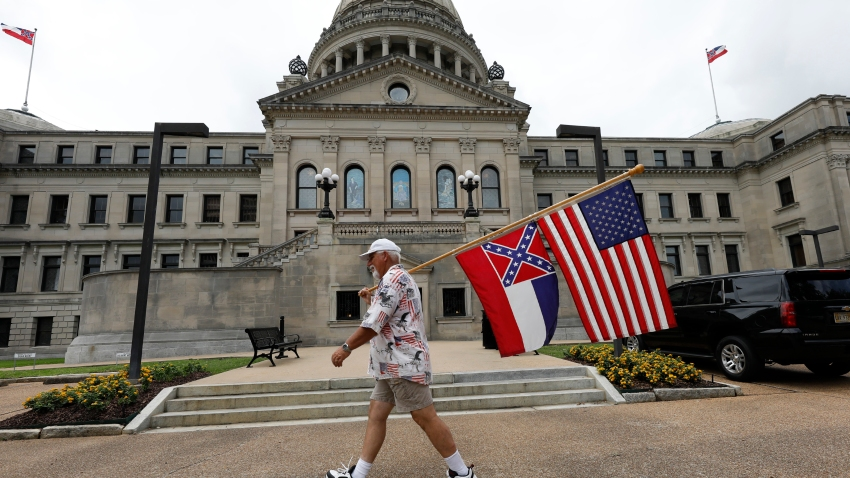 Don Hartness of Ellisville, walks around the Capitol carrying the current Mississippi state flag