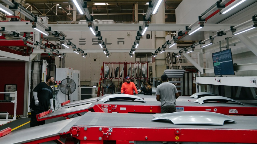 Tesla employees work to finish the upper rear trunk of the Tesla Model 3