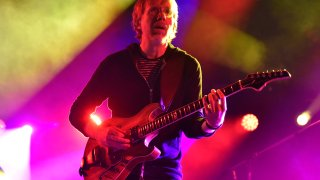 Lead singer of Phish playing a guitar.