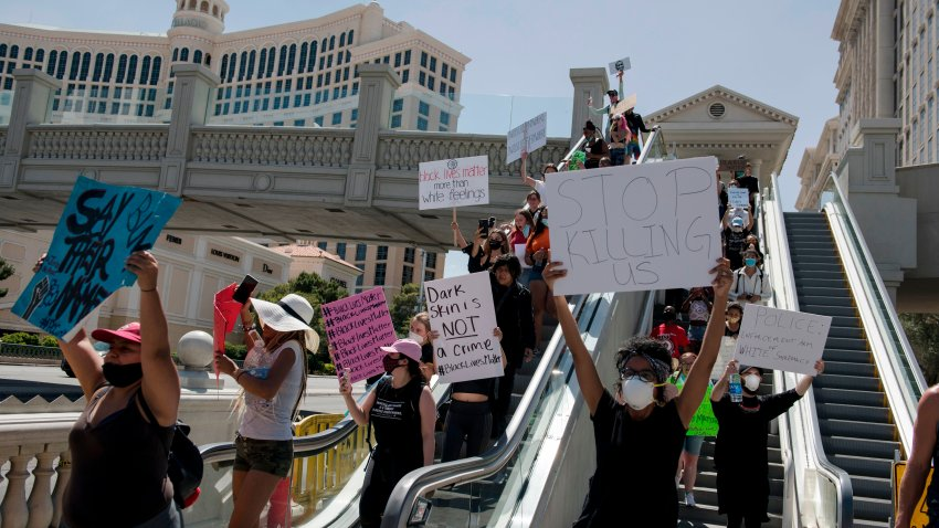 Protestors hold signs and march along the Strip in Las Vegas, Nevada on May 29, 2020, in a demonstration over the death of George Floyd, a black man who died after a white policeman kneeled on his neck for several minutes.