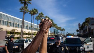 A black man and a white woman hold their hands up in a front of police officers in downtown Long Beach, California