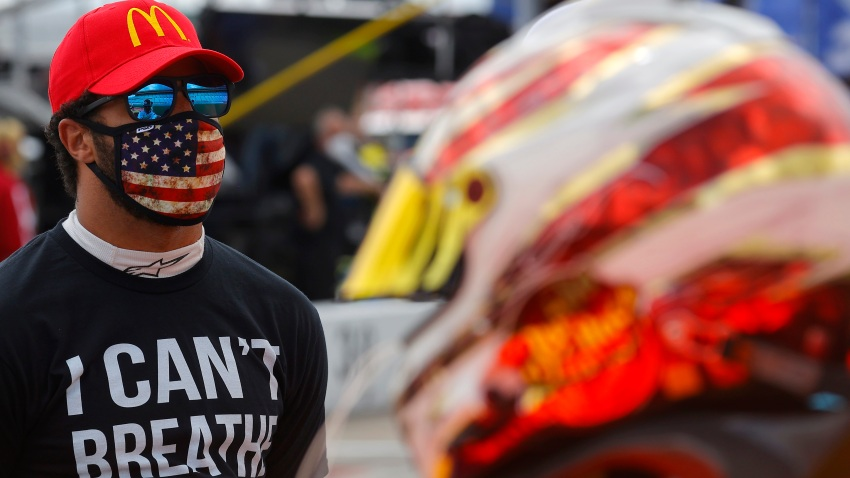 """In this June 7, 2020, file photo, Bubba Wallace wears an """"I Can't Breath - Black Lives Matter"""" T-shirt under his fire suit prior to the NASCAR Cup Series Folds of Honor QuikTrip 500 at Atlanta Motor Speedway in Hampton, Georgia."""
