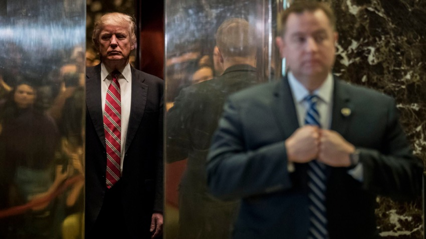 In this Jan. 16, 2017, file photo, president-elect Donald Trump heads back into the elevator after shaking hands with Martin Luther King III after their meeting at Trump Tower in New York City.