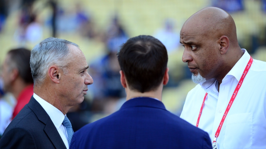 Major League Baseball Commissioner Rob Manfred Jr. talks with Executive Director of the Major League Baseball Players Association Tony Clark during batting practice prior to Game 2 of the 2017 World Series between the Houston Astros and the Los Angeles Dodgers at Dodger Stadium on Wednesday, October 25, 2017 in Los Angeles.