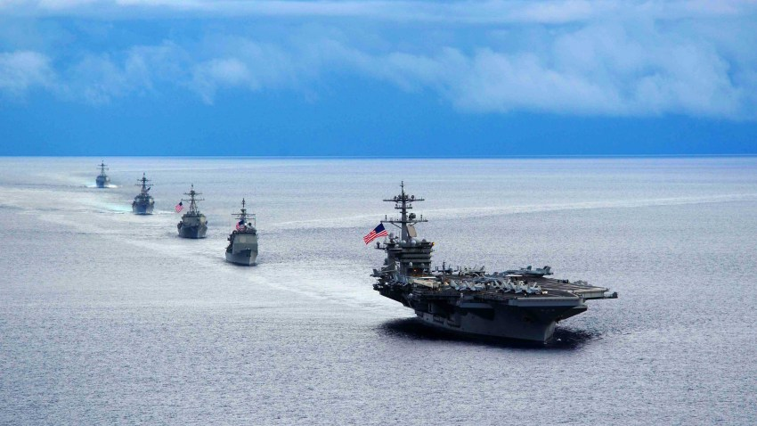 Photograph of the aircraft carrier USS Theodore Roosevelt leading a formation of ships from Carrier Strike Group during a maneuvering exercise in 2014.