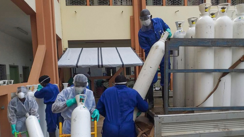 In this May 20, 2020, file photo, medical workers offload cylinders of oxygen at the Donka public hospital where coronavirus patients are treated in Conakry, Guinea. Before the coronavirus crisis,the hospital in the capital was going through20 oxygen cylinders a day. By May, the hospital was at 40 a day and rising, according to Dr.BillySivaheraofthe aid group Alliance for International Medical Action.