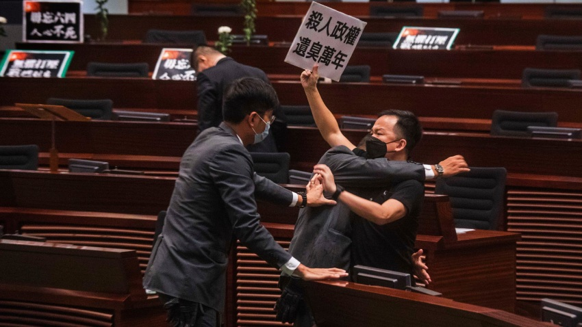 "Pan-democratic legislator Chan Chi-chuen holding a placard reading ""A murderous regime stinks for ten thousand years"" scuffles with security guards at the main chamber of the Legislative Council dropping a pot of a pungent liquid in the chamber in Hong Kong, Thursday, June 4, 2020."