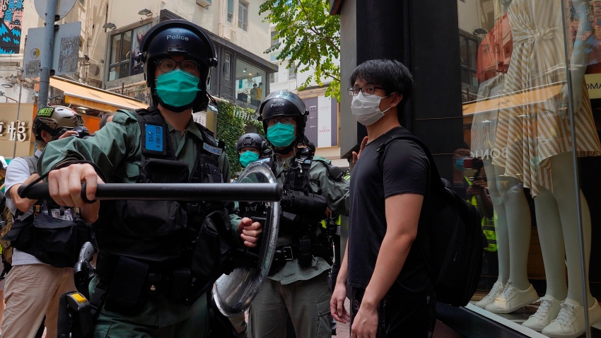 Riot police form a line as they check pedestrians gathered in the Central district of Hong Kong, Wednesday, May 27, 2020. Hong Kong police massed outside the legislature complex Wednesday, ahead of debate on a bill that would criminalize abuse of the Chinese national anthem in the semi-autonomous city.