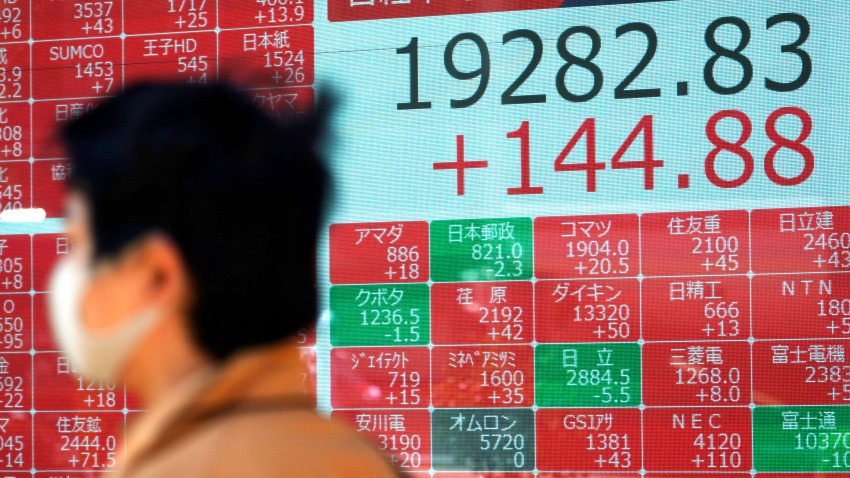 In this April 23, 2020, file photo, a man wearing a mask walks past an electronic stock board showing Japan's Nikkei 225 index at a securities firm in Tokyo.