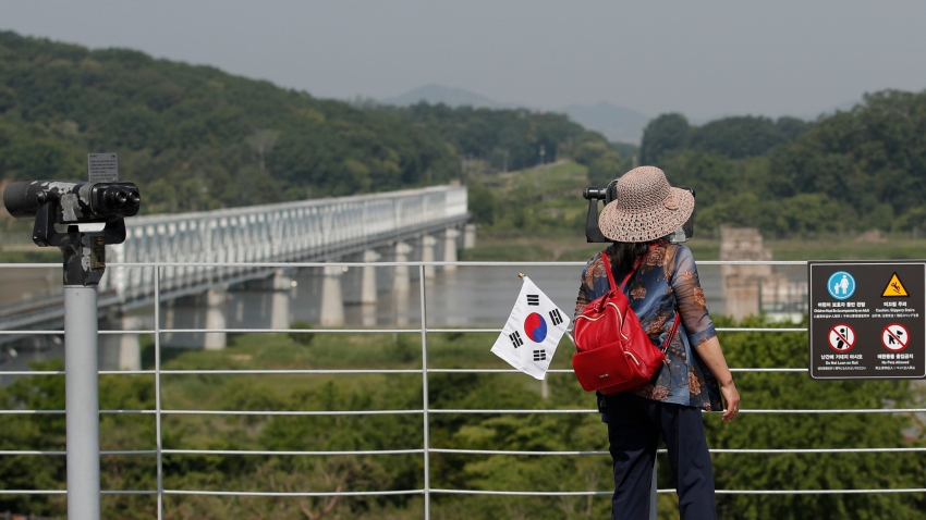 A visitor carrying a South Korean flag uses binoculars to view the northern side at the Imjingak Pavilion in Paju, South Korea, Tuesday, June 9, 2020.