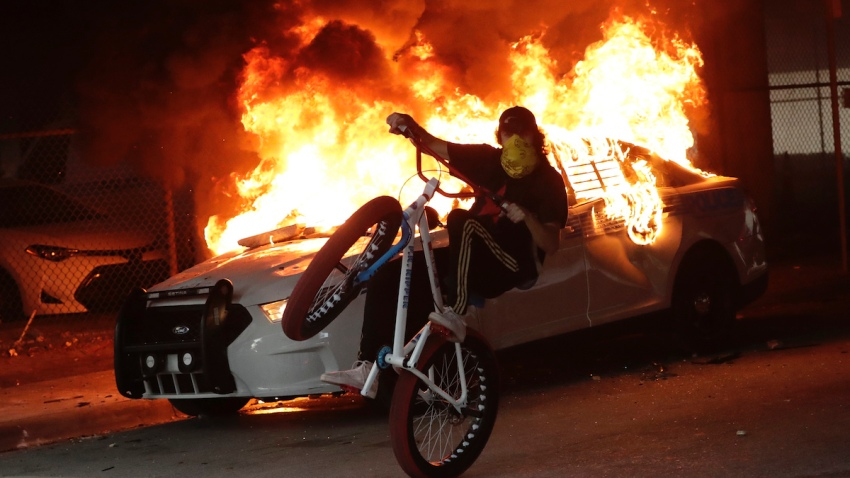 A protester on a bicycle rides past a burning police car during a demonstration next to the city of Miami Police Department, Saturday, May 30, 2020, downtown in Miami.