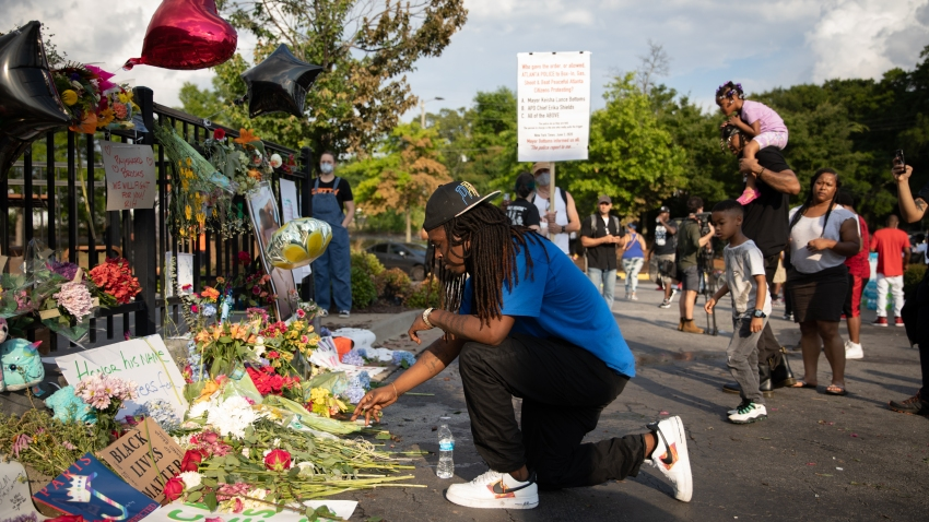 In this June 14, 2020, file photo, a man kneels at the memorial for Rayshard Brooks in Atlanta, Georgia.