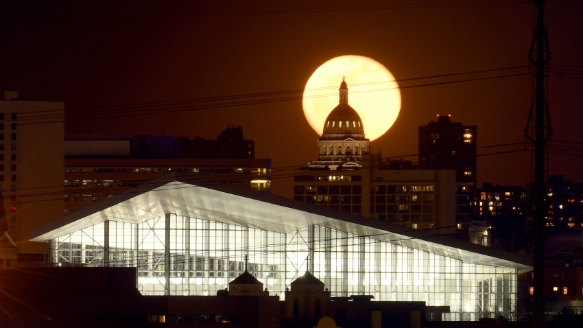 In this Wednesday, April 8, 2020 photo, the super moon rises behind the state Capitol in Denver.