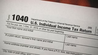 In this Dec. 22, 2017, file photo, a copy of an IRS 1040 tax form is seen at an H&R Block office in Miami, Florida.