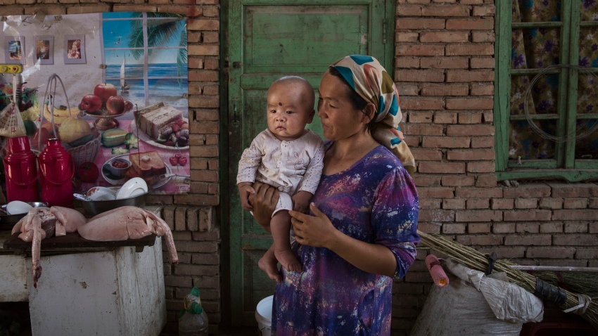 In this Sept. 12, 2016, file photo, a Uyghur woman holds a child in her home as they prepare food during the Corban Festival in Turpan County, in the far western Xinjiang province, China.