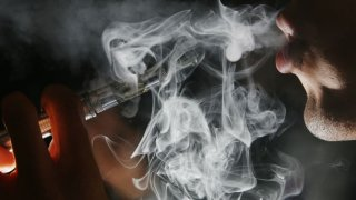 Vapor floats in the air as someone exhales after taking a puff from an e-cigarette device.
