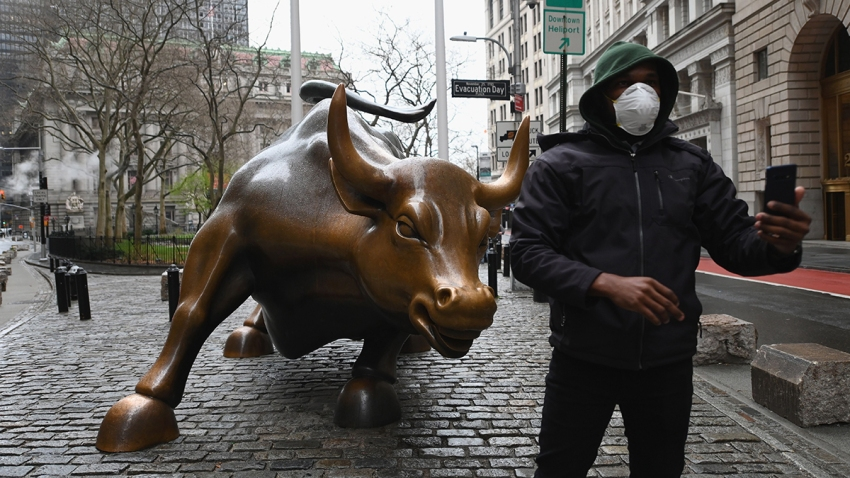 In this March 23, 2020, file photo, a man wearing a face mask takes a selfie at the Charging Bull statue outside the New York Stock Exchange in Manhattan.