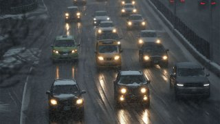 In this March 7, 2018, file photo, cars drive through wet snow along a highway in the Brooklyn borough of New York.