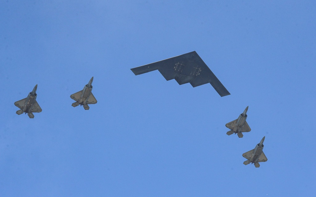 a military bomber and four fighter jets fly over boston on july 4