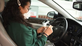 A woman with a face mask sits in her car and holds a nasal swab at a CVS coronavirus drive-thru testing site.