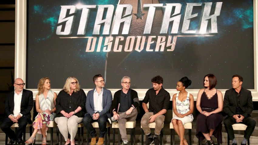 """In this Aug. 1, 2017, file photo, (L-R) executive producers Akiva Goldsman, Heather Kadin, Gretchen Berg, Aaron Harberts, and Alex Kurtzman, and actors James Frain, Sonequa Martin, Mary Chieffo, and Jason Isaacs of """"Star Trek: Discovery"""" speak onstage during the CBS portion of the 2017 Summer Television Critics Association Press Tour at CBS Studio Center in Los Angeles, California."""