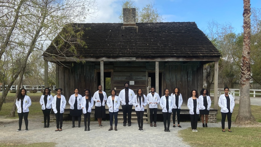 Students from Tulane University's medical school stand in front of former slave quarters at the Whitney Plantation in Wallace, Louisiana, Dec. 14, 2019.
