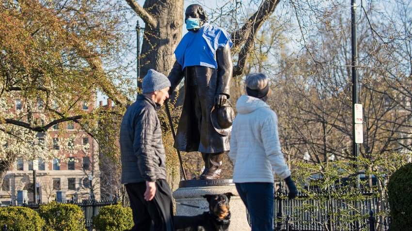 This April 17, 2020, file photo shows a mask and medical shirt draped over the statue of historian and minister Edward Everett Hale in an empty Boston Public Garden.