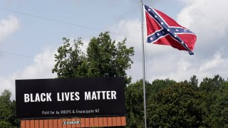 A Black Lives Matter billboard is seen next to a Confederate flag in Pittsboro, N.C., Thursday, July 16, 2020. A group in North Carolina erected the billboard to counter the flag that stands along the road.