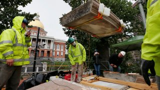 """Workers inspect the top cornice stone as it is lifted from the Shaw 54th Regiment memorial opposite the Statehouse, Friday, July 17, 2020, in Boston. Amid the national reckoning on racism, the memorial to the first Black regiment of the Union Army, the Civil War unit popularized in the movie """"Glory,"""" is facing scrutiny."""