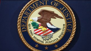 FILE - The Department of Justice seal is seen on a lectern ahead of a press conference in Washington, D.C., Nov. 28, 2018.