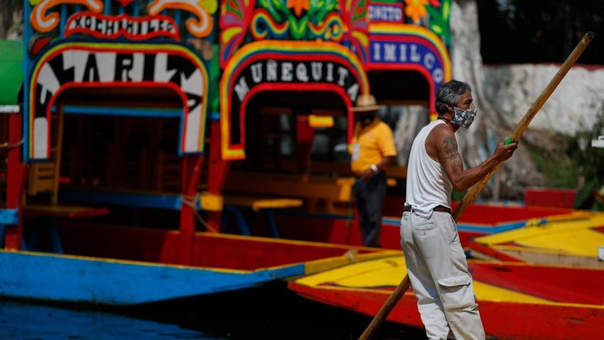 A gondolier poles one of the colorfully painted wooden boats known as trajineras at the Nuevo Nativitas dock at Xochimilco
