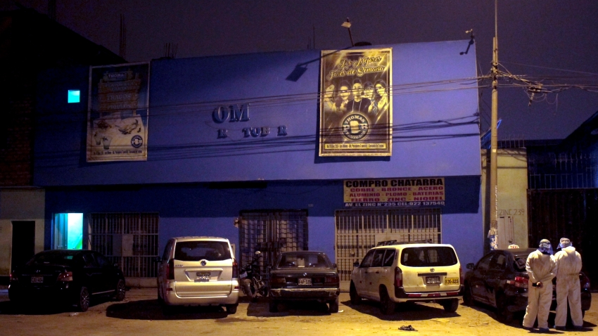 Police officers, wearing protective clothing, stand outside a disco in Lima, Peru, Sunday, Aug. 23