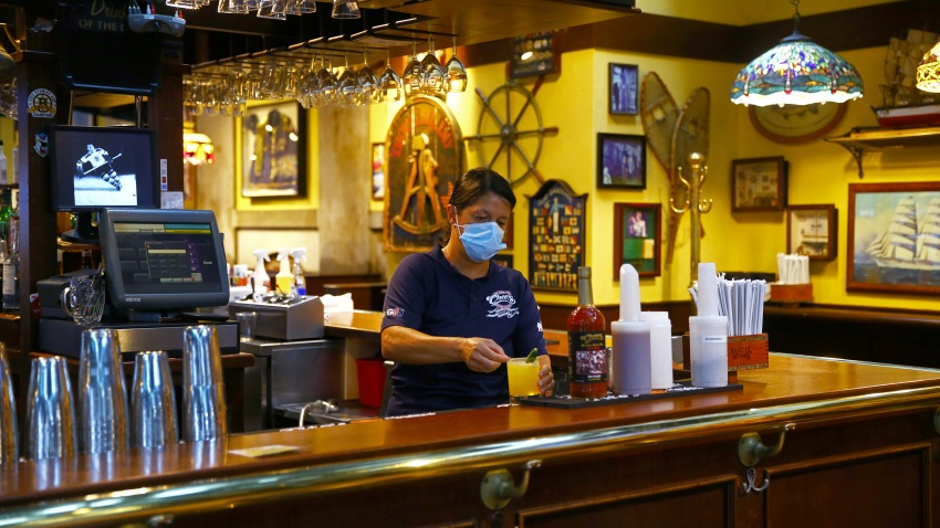 A bartender in Cheers finishes a drink order at Quincy Market in Boston on July 1, 2020.