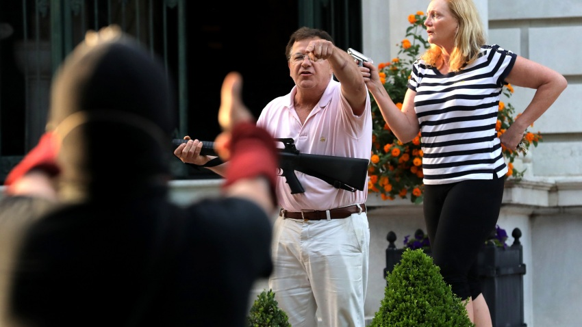 Armed homeowners Mark T. and Patricia N. McCloskey stand in front their house along Portland Place as they confront protesters marching to St. Louis Mayor Lyda Krewson's house Sunday, June 28, 2020, in the Central West End of St. Louis.
