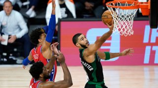 Jayson Tatum #0 of the Boston Celtics drives to the basket against Joel Embiid #21 and Matisse Thybulle #22 of the Philadelphia 76ers during the first half at The Field House at ESPN Wide World Of Sports Complex on August 17, 2020 in Lake Buena Vista, Florida.