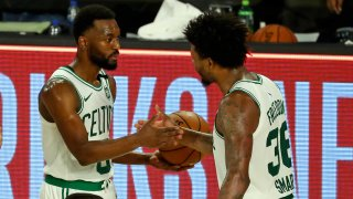 Kemba Walker #8 and Marcus Smart #36 of the Boston Celtics celebrate their 102-94 victory over the Philadelphia 76ers in Game 3 of the first round of the NBA Playoffs at The Field House at ESPN Wide World Of Sports Complex on August 21, 2020 in Lake Buena Vista, Florida.