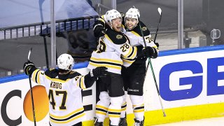 Jake DeBrusk #74 of the Boston Bruins is congratulated by his teammates after scoring a goal at 14:17 against the Carolina Hurricanes during the third period in Game Four of the Eastern Conference First Round during the 2020 NHL Stanley Cup Playoffs at Scotiabank Arena on August 17, 2020 in Toronto, Ontario.
