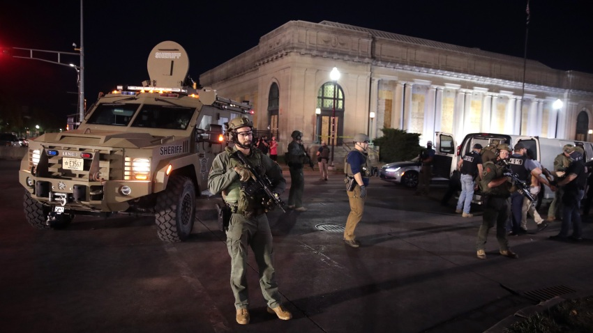 Police officers keeps watch as people are arrested after the start of a city-wide curfew outside of the Kenosha County Courthouse on August 29, 2020 in Kenosha, Wisconsin.
