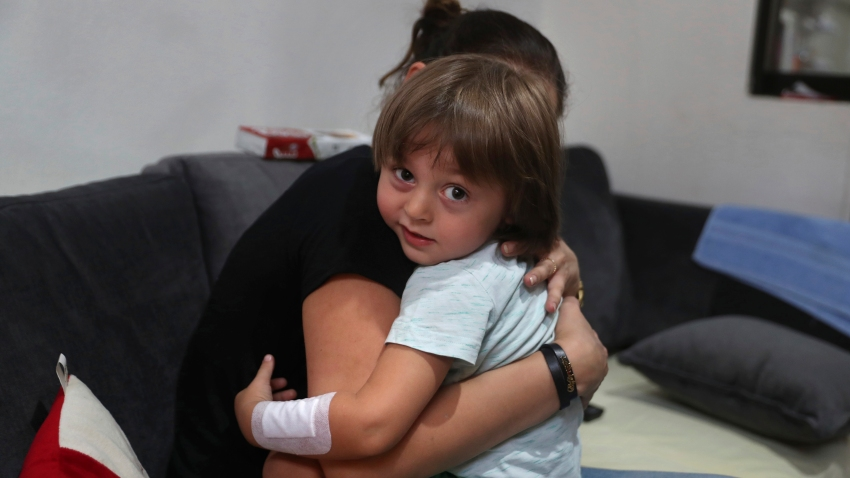 Hiba Achi hugs her son, three-year-old Abed Achi, at her house in Beirut, Lebanon, Tuesday, Aug. 11, 2020. Abed was playing with his Lego blocks when the huge blast ripped through Beirut, shattering the nearby glass doors.